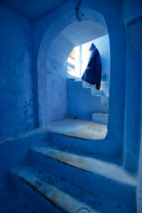 Morocco, Chefchaouen, Person in blue robe on whitewashed steps