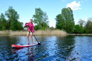 Woman stand up paddling on Lake Staffelsee, Bavaria, Germany