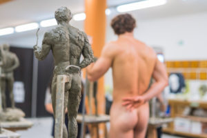 Sculpture and naked model in the background