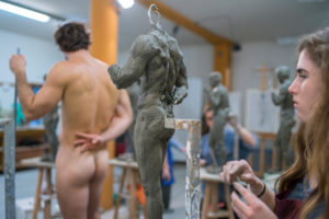Female student working at sculpture, nude model in the background
