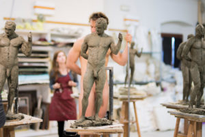 Sculptures in the foreground, nude model in the background during class