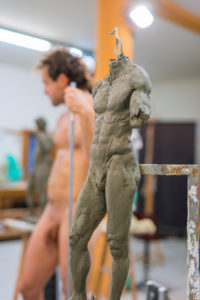 Nude model during class, focus on sculpture in foreground