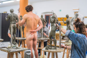 Female student forming sculpture, nude model in the background