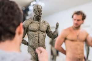 Student forming sculpture, naked model in the background