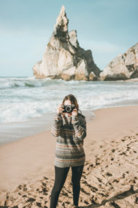 Young woman photographing while standing against rock formation at beach, Praia da Ursa, Lisboa, Portugal