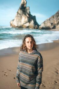 Beautiful young woman standing against rock formation at Praia da Ursa, Lisboa, Portugal
