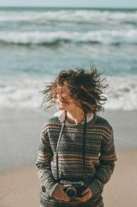 Young woman standing with tousled hair against sea, Praia da Ursa, Lisboa, Portugal