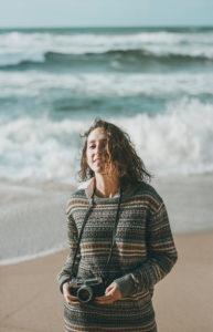 Beautiful young woman standing with camera at beach, Praia da Ursa, Lisboa, Portugal