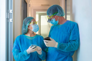 Male and female dentists discussing while standing at doorway in clinic