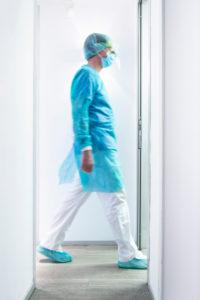 Mature male dentist walking in illuminated hallway at clinic
