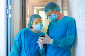 Mature male and female dentists discussing over smart phone while standing at doorway in clinic