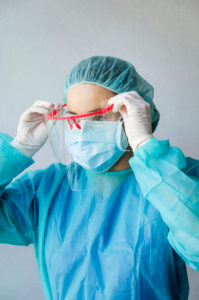 Mature female dentist wearing protective face shield with scrubs at clinic