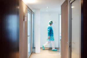 Mature male dentist walking in illuminated hallway at medical clinic
