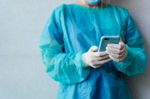 Mature female dentist text messaging while standing against white wall at clinic
