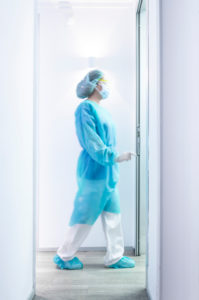 Mature female dentist walking in illuminated hallway