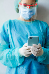 Female dentist using mobile phone while standing at clinic