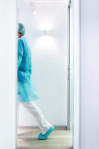 Mature male dentist walking in illuminated hallway