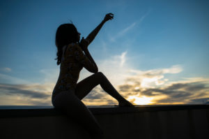 Full length side view of woman sitting on retaining wall at building terrace during sunset