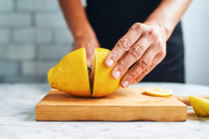 Hands of woman cutting lemons on cutting board