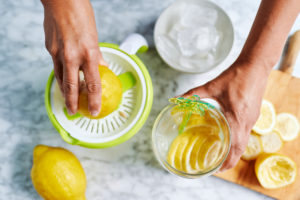 Hands of woman squeezing lemons with juicer