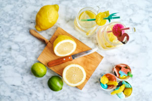 Cutting board, kitchen knife, lemons, limes, gummy candies and jars of fresh homemade lemonade