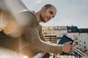 Man leaning on balcony railing, holding digital tablet