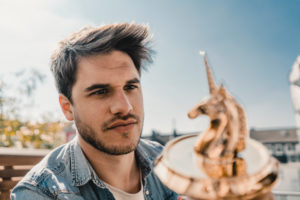 Young entrepreneur looking at unicorn figurine