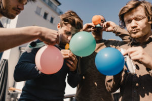 Group of friends playing with balloons ona balcony