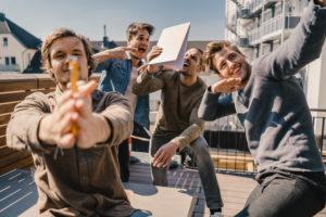 Young entrepreurs having fun on a balcony, celebrating success