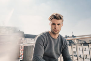Portrait of cool young man sitting on balcony