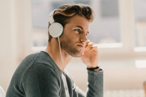 Young man in office wearing headphones