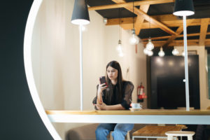 Confident young woman using smart phone while sitting at coffee shop