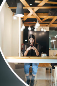 Full length of confident young woman using mobile phone while sitting at illuminated cafeteria