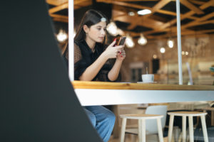 Beautiful young woman using mobile phone while sitting at illuminated coffee shop