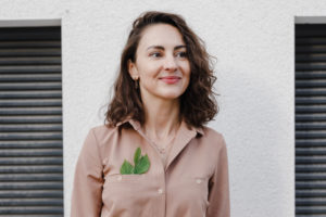 Thoughtful of businesswoman with leaves in pocket standing against wall