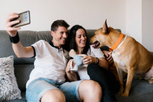 Smiling couple taking selfie with dog at home