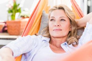 Portrait of pensive mature woman relaxing in hammock