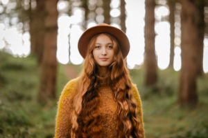 Beautiful woman with long hair wearing hat standing in forest