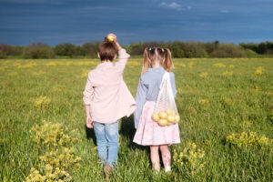 Elementary siblings standing with fresh lemons while standing at rape field on sunny day