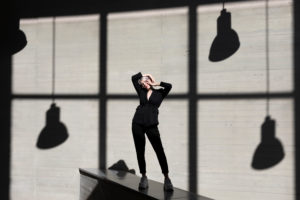 Stylish businesswoman wearing suit standing on retaining wall with sunlight and shadow in background