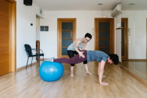 Physiotherapist assisting patient in balancing on fitness ball at health club