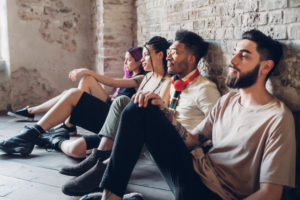 Group of friends sitting on the floor in a loft