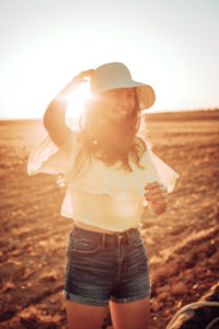 Cheerful young woman standing on field against sky during sunset