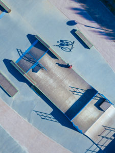 Man sitting on concrete ramp in skate park, aerial view