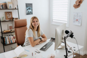 Smiling businesswoman using computer on desk at home