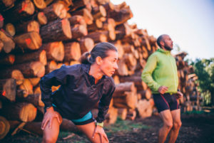 Mature couple exercising while standing against logs