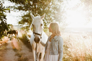 Woman with grey horse on a farm