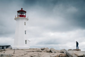 Man standing near Peggys Point Lighthouse on rock formation against cloudy sky, Nova Scotia, Canada