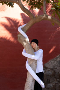 Thoughtful woman with artificial long hands embracing tree trunk against wall