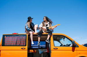 Two women sitting on roof of van, playing guitar